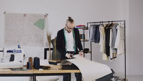 有磁带线路的年轻男性设计师在他的站立在女装裁制业演播室和裁减的脖子与剪刀一个样式新的 股票录像