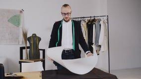 有磁带线路的年轻男性设计师在她的站立在女装裁制业演播室的脖子和得出在纸的一个样式 男 影视素材