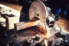 有磨床的,电动工具工作者在工厂 切口钢和铁细节  免版税图库摄影