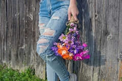 有磨损的牛仔裤和雏菊的青少年的女孩 库存图片