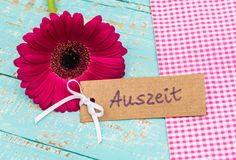 有礼品券和德国词的, Auszeit,手段暂停洋红色开花或放松 库存图片