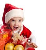 有礼品圣诞节球和帽子的小女孩 免版税库存照片