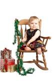 有礼品岩石的圣诞节婴孩在补缀品礼服 免版税库存图片
