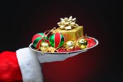 有礼品的圣诞老人在盘 免版税图库摄影