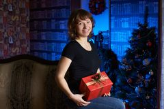 有礼品的女孩 圣诞节内部 库存图片