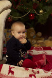 有礼品的女婴在圣诞树下 免版税库存照片