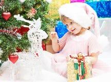 有礼品的小女孩在圣诞节或新年度 免版税库存照片