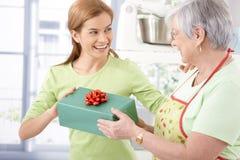 有礼品的愉快的女性存在的母亲 免版税库存图片