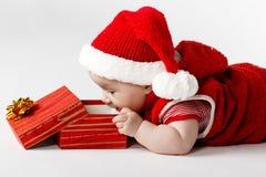 有礼品的逗人喜爱的圣诞节婴孩 免版税库存照片