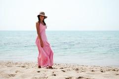有礼服的美丽的妇女在一个热带海滩 库存图片