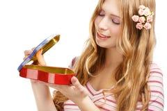 有礼物心脏形状箱子的美丽的年轻微笑的妇女 免版税库存图片