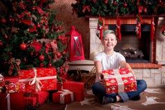 有礼物的一个男孩在圣诞树附近坐 免版税库存图片