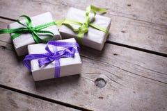 有礼物的三个欢乐礼物盒在年迈的木backgroun 免版税库存图片