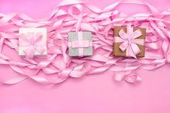 有礼物的三个箱子在桃红色颜色装饰缎丝带的革命的背景  库存照片