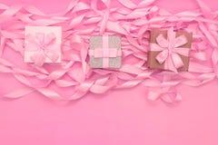 有礼物的三个箱子在桃红色颜色装饰缎丝带的革命的背景  免版税库存照片