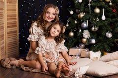 有礼物的两个姐妹临近圣诞树 免版税库存图片