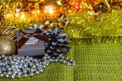 有礼物的五颜六色的小礼物盒在圣诞节闪亮金属片中和发光的玩具和装饰 免版税库存照片