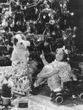 有礼物的十几岁的女孩在圣诞树下(所有人被描述不更长生存,并且庄园不存在 供应商warran 免版税库存图片