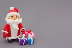 有礼物的圣诞老人在黏土外面 免版税库存图片