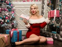 有礼物的圣诞节女孩在圣诞树附近 作为加工好的圣诞老人妇女 免版税库存照片