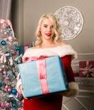 有礼物的圣诞节女孩在圣诞树附近 作为加工好的圣诞老人妇女 免版税库存图片