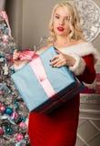 有礼物的圣诞节女孩在圣诞树附近 作为加工好的圣诞老人妇女 库存图片