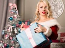 有礼物的圣诞节女孩在圣诞树附近 作为加工好的圣诞老人妇女 免版税图库摄影