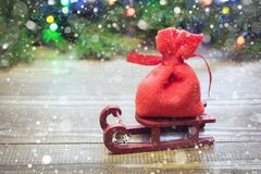 有礼物的圣诞节红色大袋在木背景的雪撬与云杉的分支和诗歌选 免版税库存照片