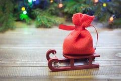 有礼物的圣诞节红色大袋在木背景的雪撬与云杉的分支和诗歌选 库存照片