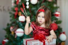 有礼物的女孩在圣诞树附近 免版税库存图片