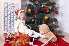 有礼物的女孩在圣诞节冷杉木下 免版税库存图片