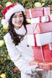 有礼物的女孩临近圣诞树 免版税图库摄影