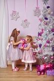 有礼物的姐妹临近圣诞树 免版税图库摄影