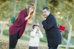 有礼物的嬉戏的Mixedrace父母年轻男孩掩藏的眼睛的 库存图片