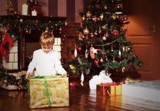 有礼物的小男孩在圣诞节 免版税图库摄影