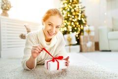 有礼物的愉快的妇女在圣诞树附近的早晨 免版税库存图片