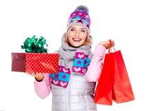 有礼物的愉快的妇女在购物以后对新年 免版税库存照片