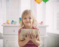 有礼物的愉快的小女孩庆祝她的生日的 图库摄影