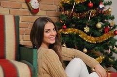 有礼物的愉快的微笑的少妇临近圣诞树在h 免版税库存图片