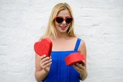 有礼物的愉快的美丽的女性为在轻的墙壁背景,特写镜头的情人节 库存照片