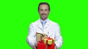 有礼物的成熟医生与丝带弓 股票录像