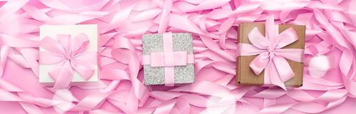 有礼物的横幅三箱子在桃红色颜色装饰缎丝带的革命的背景  图库摄影