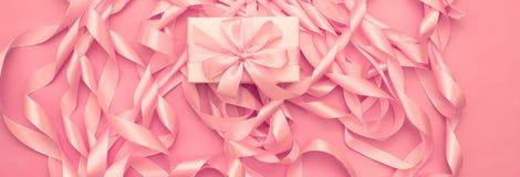 有礼物的横幅箱子在桃红色颜色装饰缎丝带卷的背景  免版税库存图片