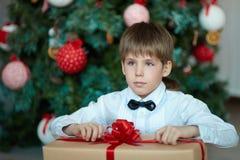有礼物的男小学生在圣诞树 免版税库存图片