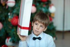 有礼物的男小学生在圣诞树 图库摄影
