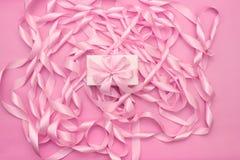 有礼物的箱子在桃红色颜色装饰缎丝带卷的背景  免版税图库摄影
