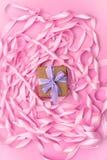 有礼物的箱子在桃红色颜色装饰缎丝带卷的背景  免版税库存照片