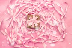 有礼物的箱子在桃红色颜色装饰缎丝带卷的背景  免版税库存图片