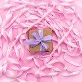 有礼物的箱子在桃红色颜色装饰缎丝带卷的背景  图库摄影