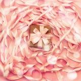 有礼物的箱子在桃红色颜色装饰缎丝带卷的背景  库存照片